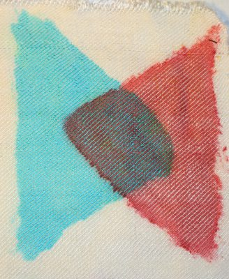 triangle in turquoise fiber-reactive dye, overlapped by triangle in red acid dye