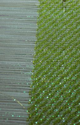 early part of the weaving, green tencel and gold embroidery thread weft, showing the sparkle of the opalescent transparent nylon thread