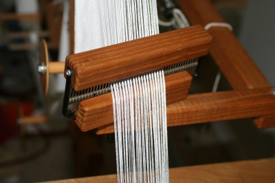 The warping wheel comb, with the peg only partially inserted so it doesn't split the yarn as it winds on.