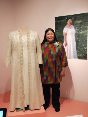 Tien with her wedding dress at the museum exhibit