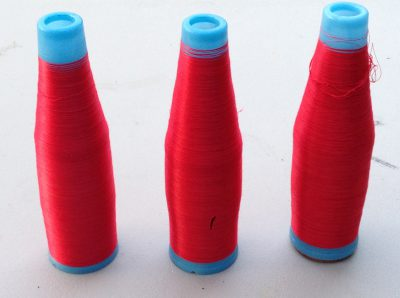 three cones of fine silk yarn