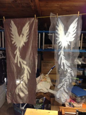 stenciled warp, fully woven, with stencil hanging beside it