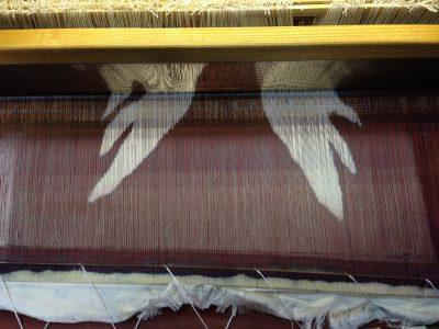 stenciled warp, before being woven