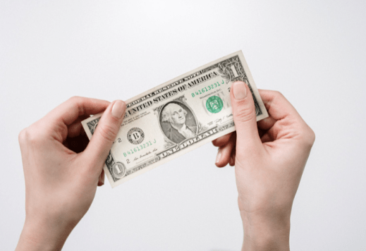 photo of hands holding a dollar bill
