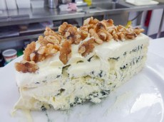 large wedge of layered blue and marscapone cheesewith walnuts on top