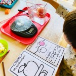 Child in the middle of fun apple activities for preschoolers. Investigate an apple by weighing, observing, drawing, and recording your findings of an apple.
