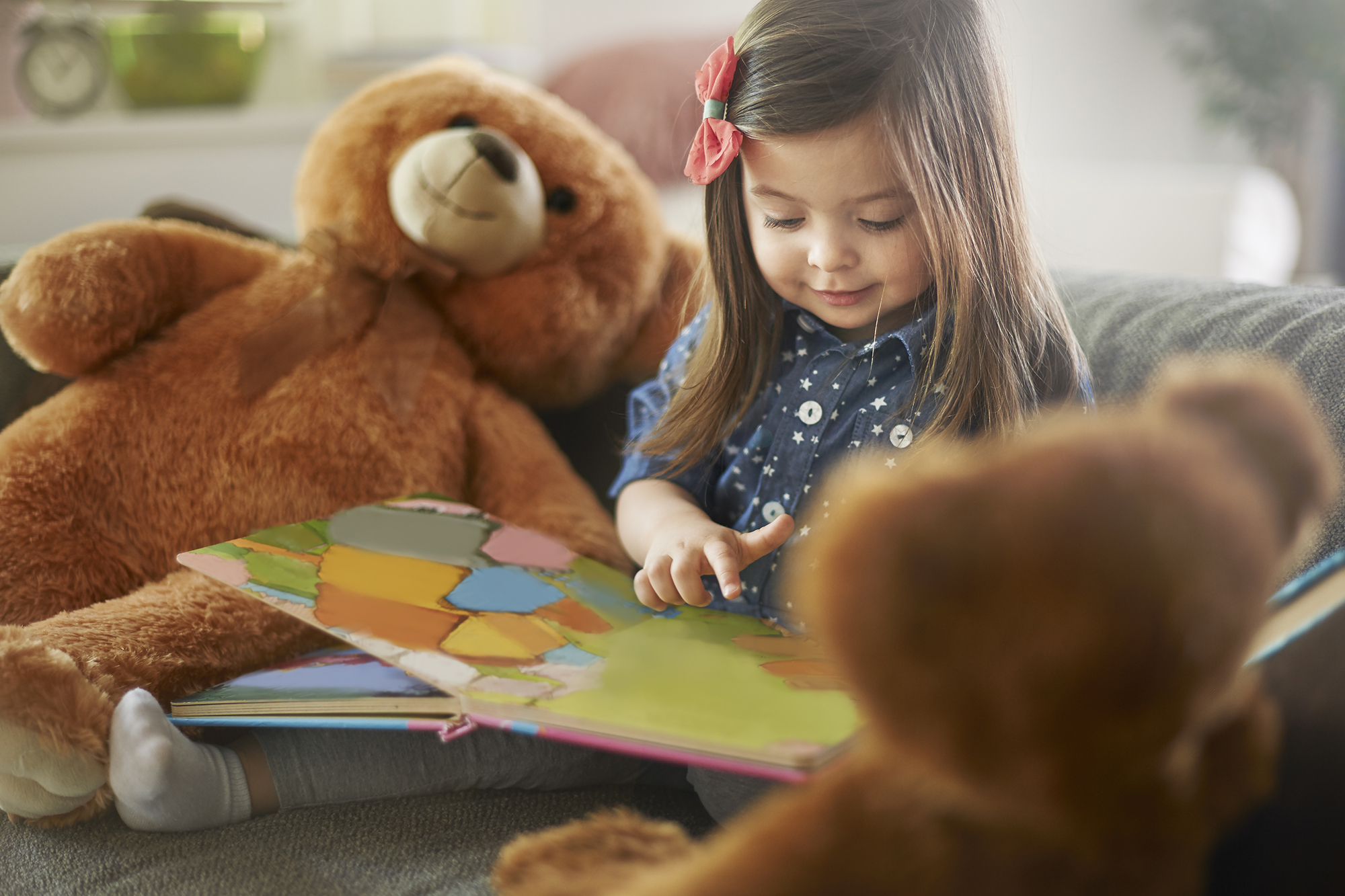 Toddler girl reading a book on a sofa surrounded by teddy bear stuffed animal