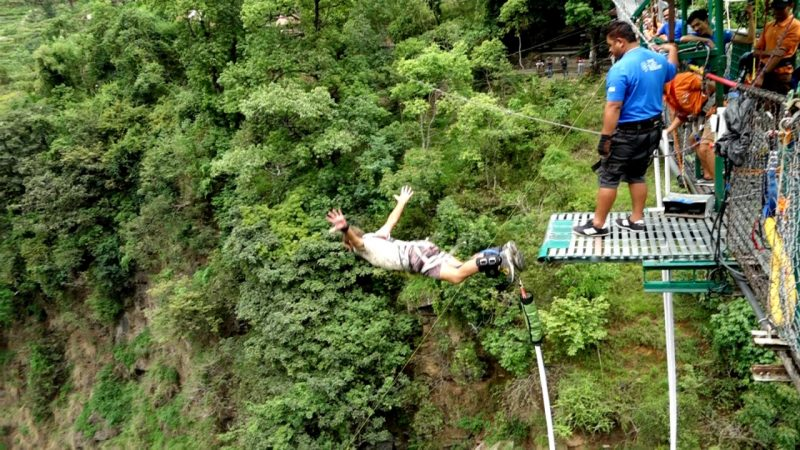 man bungy jumping from bridge