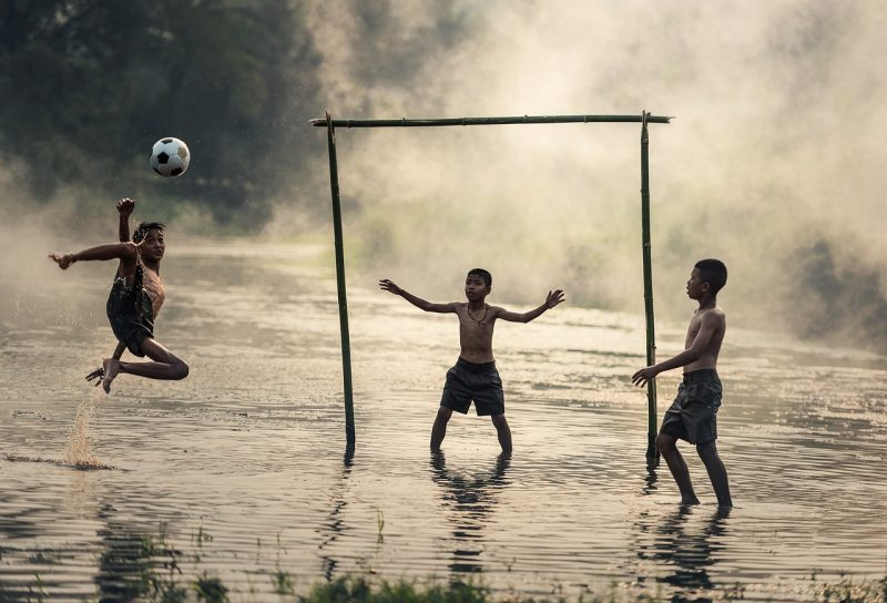 three kids playing football in monsoon