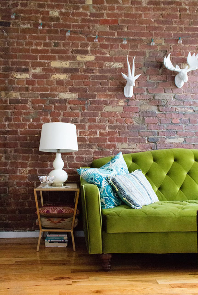 greenery sofa with brick wall