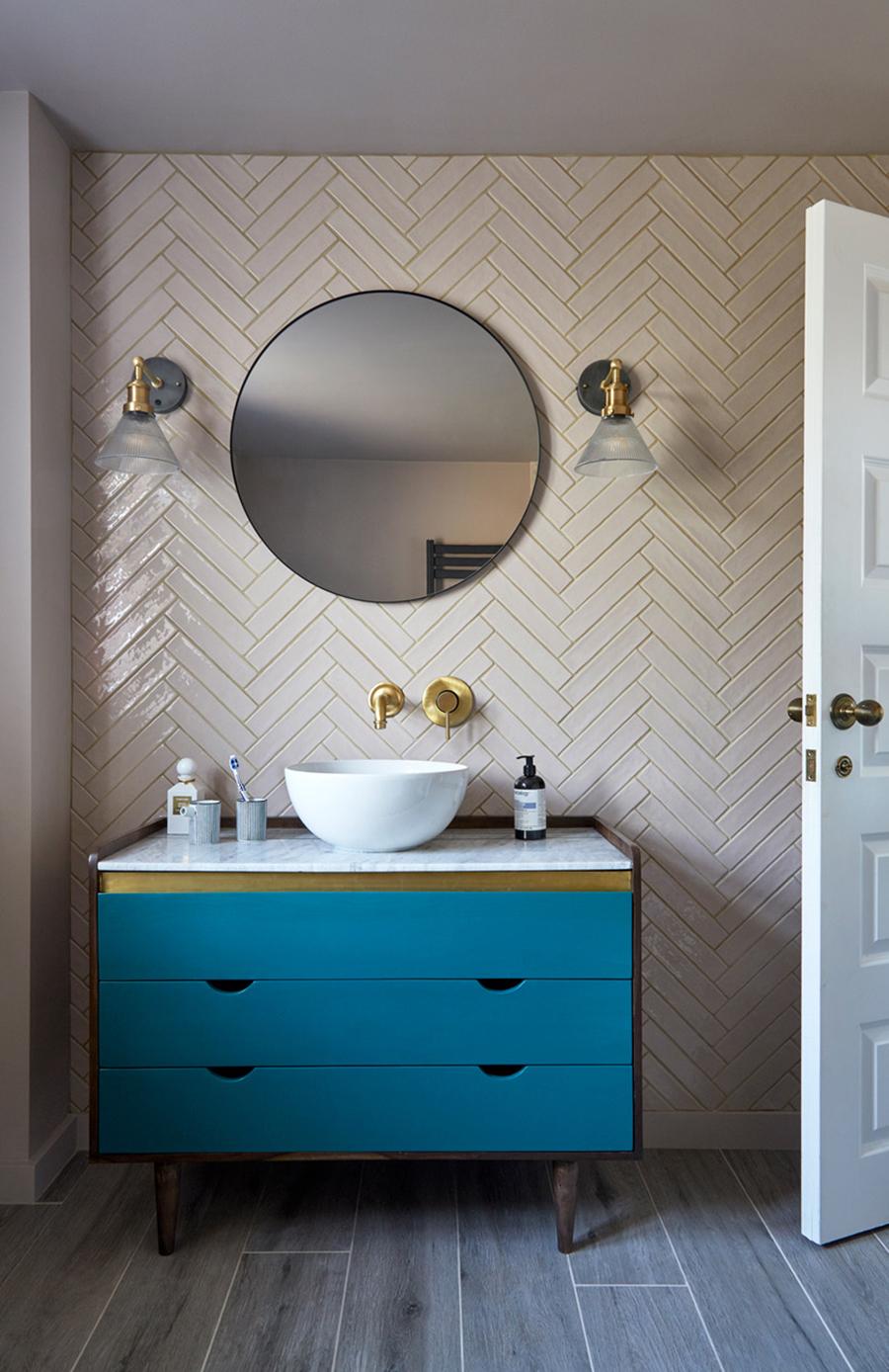 Herringbone pattern tiles with blue vanity contemporary bathroom design