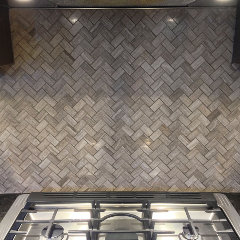 Wooden White Marble Herringbone Mosaic installed above a stove