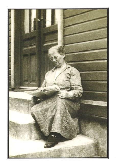 Anna Sophie leser avisen på trappen utenfor huset sitt.