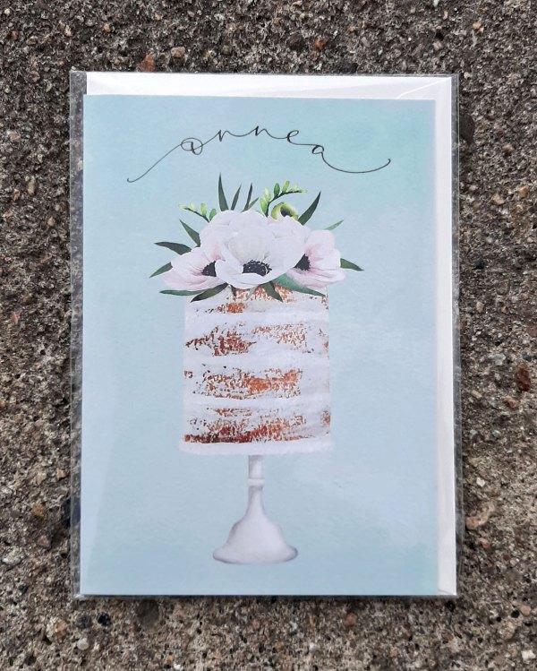Kaksiosainen onnittelukortti, jossa kannessa kakku ja teksti Onnea. Suunnittelija Henna Adel