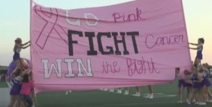 """Cheerleaders hold a banner before the Oct. 1 """"Pink Out"""" varsity football game."""