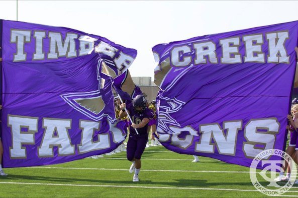 Timber Creek players bust through a banner before the Sept. 2, 2017 home opener. (Photo by Yearbook Editor Taylor Deker.)