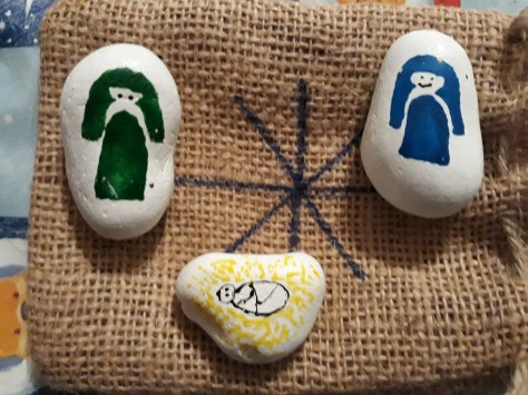Stones painted to look like the Holy Family (Mary, Joseph and Jesus) resting on a hessian bag