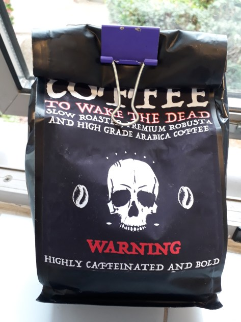 Bag of coffee closed with a purple folding bulldog clip