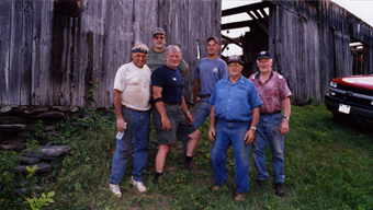 Volunteer workers posing in front of the barn.