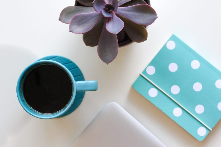 Coffee and notebook belonging to a virtual assistant and online business manager