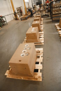 """The top of the mold, called the """"cope,"""" is lowered onto the drag after loading in the sand cores. Since metal is poured into the cope, it houses the sprue and risers. Sadly, the artfully sculpted sand molds and cores must be destroyed in order to punch out the cylinder head after the metal cools."""