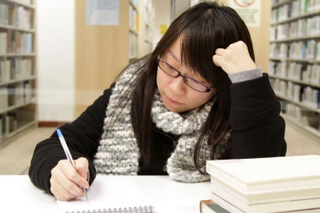 Female student reading and studying in library