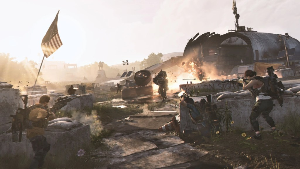 The Division 2 screenshot - remains of a downed passenger plane in the background with a heavily armored enemy being fought by two division agents.