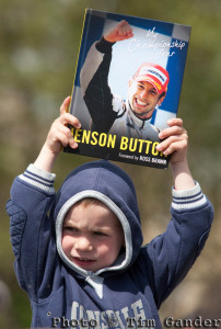 Boy awaits arrival of Jenson Button, holding Jenson Button book.