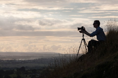 Photographer Tim Gander sits with his camera on a tripod on the side of a hill