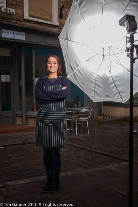 Waitress poses in the street in front of a photo flash on a stand with a white brolly