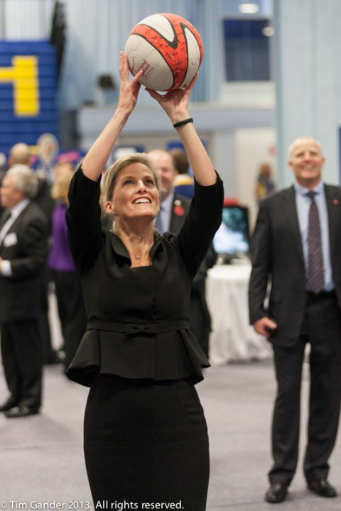 Sophie Wessex smiles as she holds a netball aloft and aims to take a shot at the net