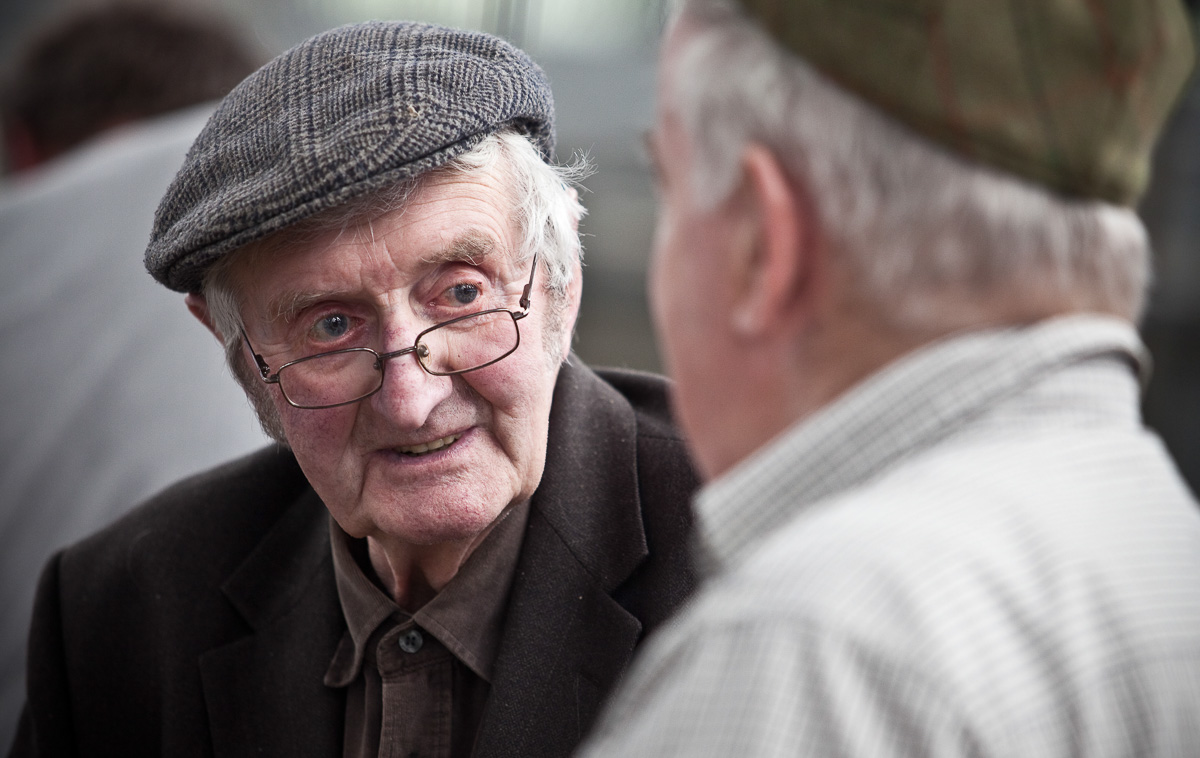 Close view of two farmers having a conversation. A farmer on the left is looking to an out-of-focus figure who we can only see the back of the head and shoulder of.