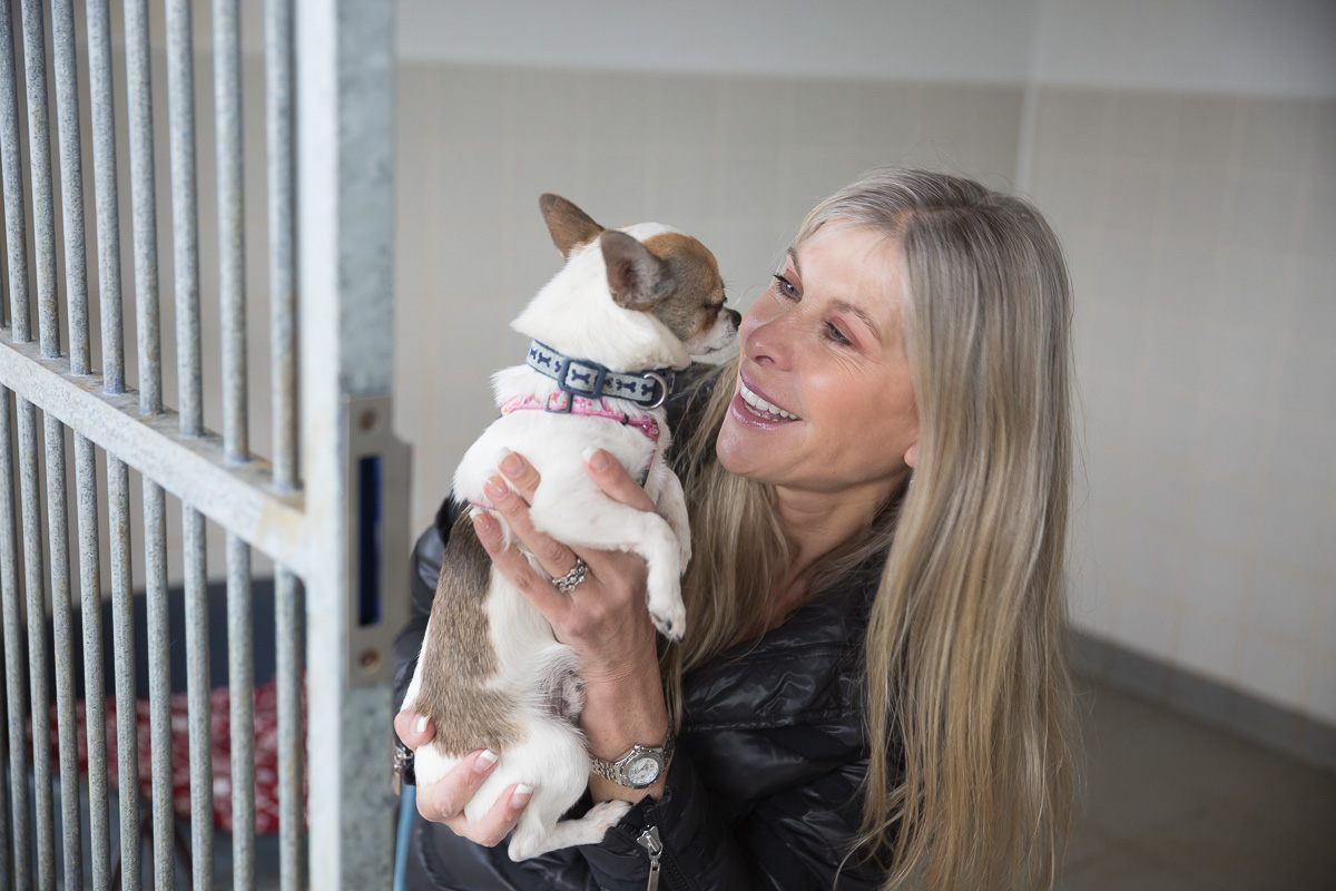 Olympic swimmer Sharron Davies holds a small dog in her hands and smiles into its face.