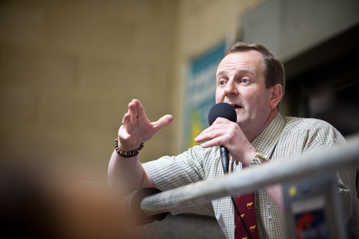 Close view of the auctioneer holding a microphone and gesticulating with his hand as he takes bids.