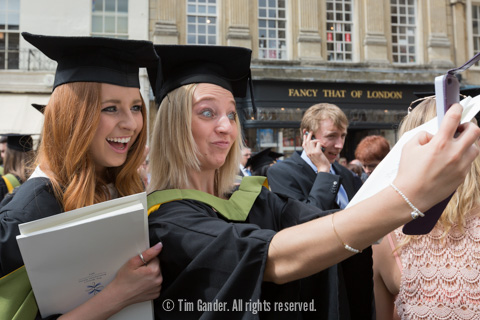 Two female students make a selfie while smiling and pulling funny faces