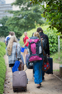 School pupils in casual clothes arrive at University of Bath campus with suitcases