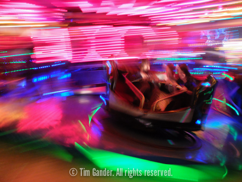 blurred, colourful photo of fairground waltzers ride