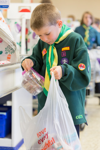Eight-year-old Scout Adam Henderson concentrates on packing customer bags for charity at Tesco's store in Salisbury