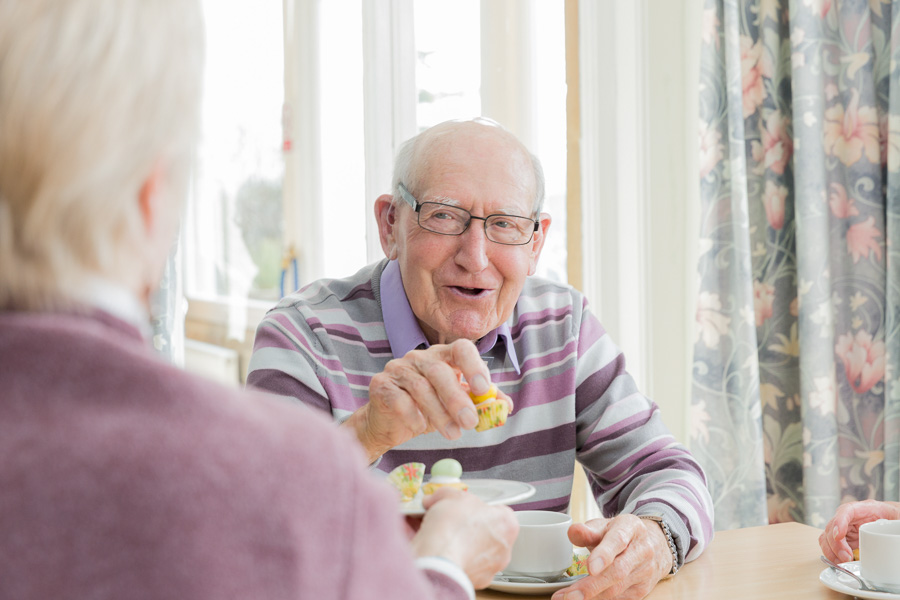 An elderly gentleman smiles and shares tea and cake with a friend who sits with their back to the camera.