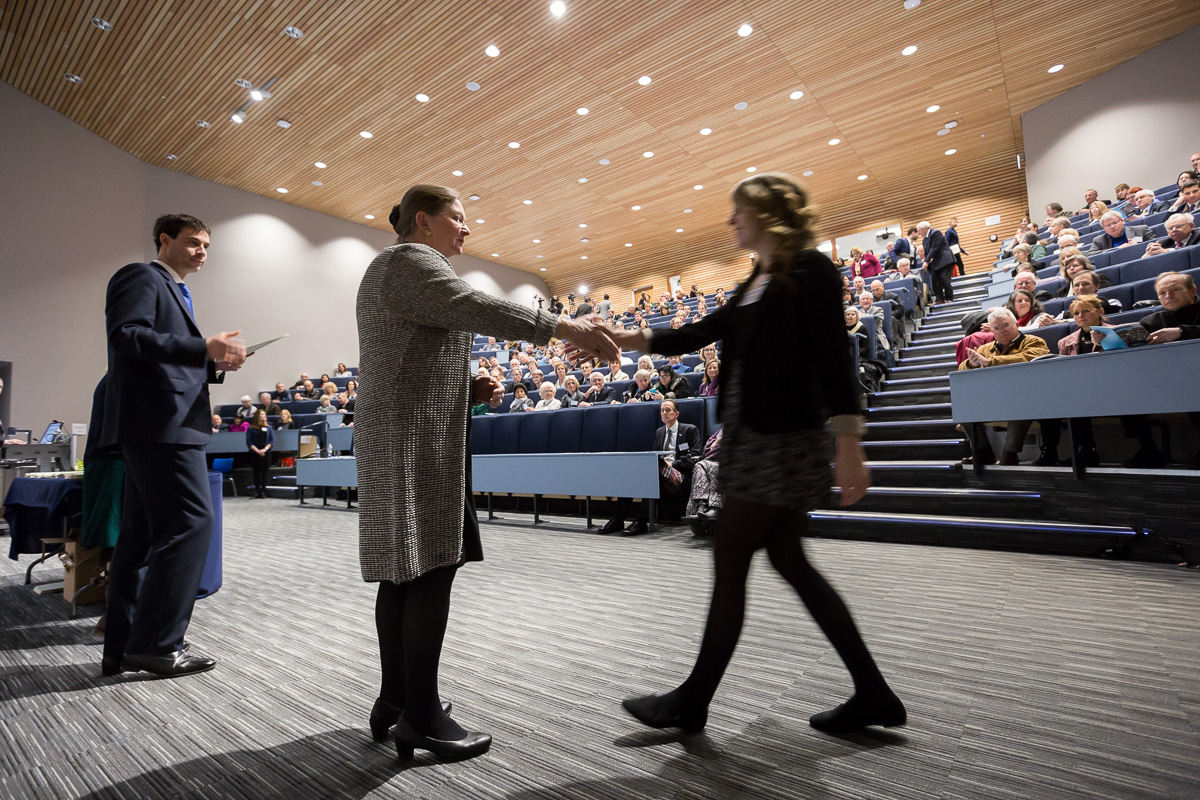 Vice Chancellor of University of Bath Glynis Breakwell shakes the hand of a student as she steps forward to receive her scholarship certificate in a packed lecture theatre.