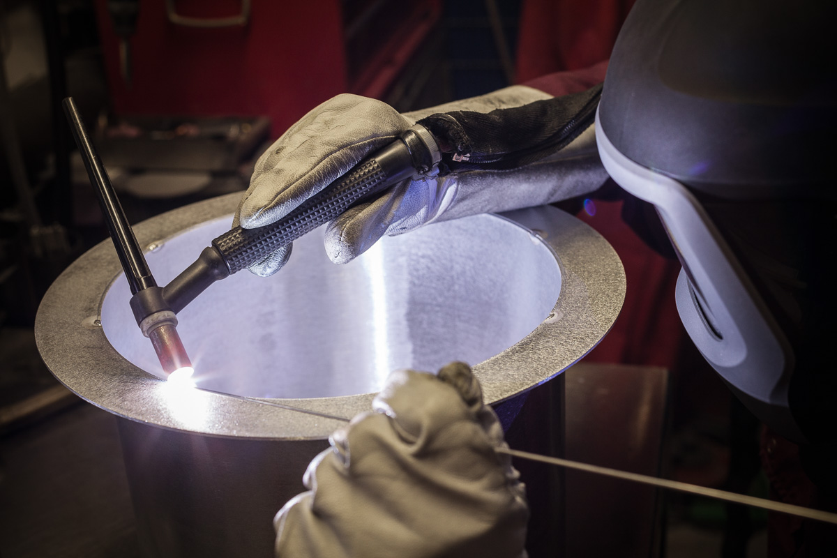 A welding engineer uses welding torch and flux rod to weld a steel collar to a tubular section of pipe.