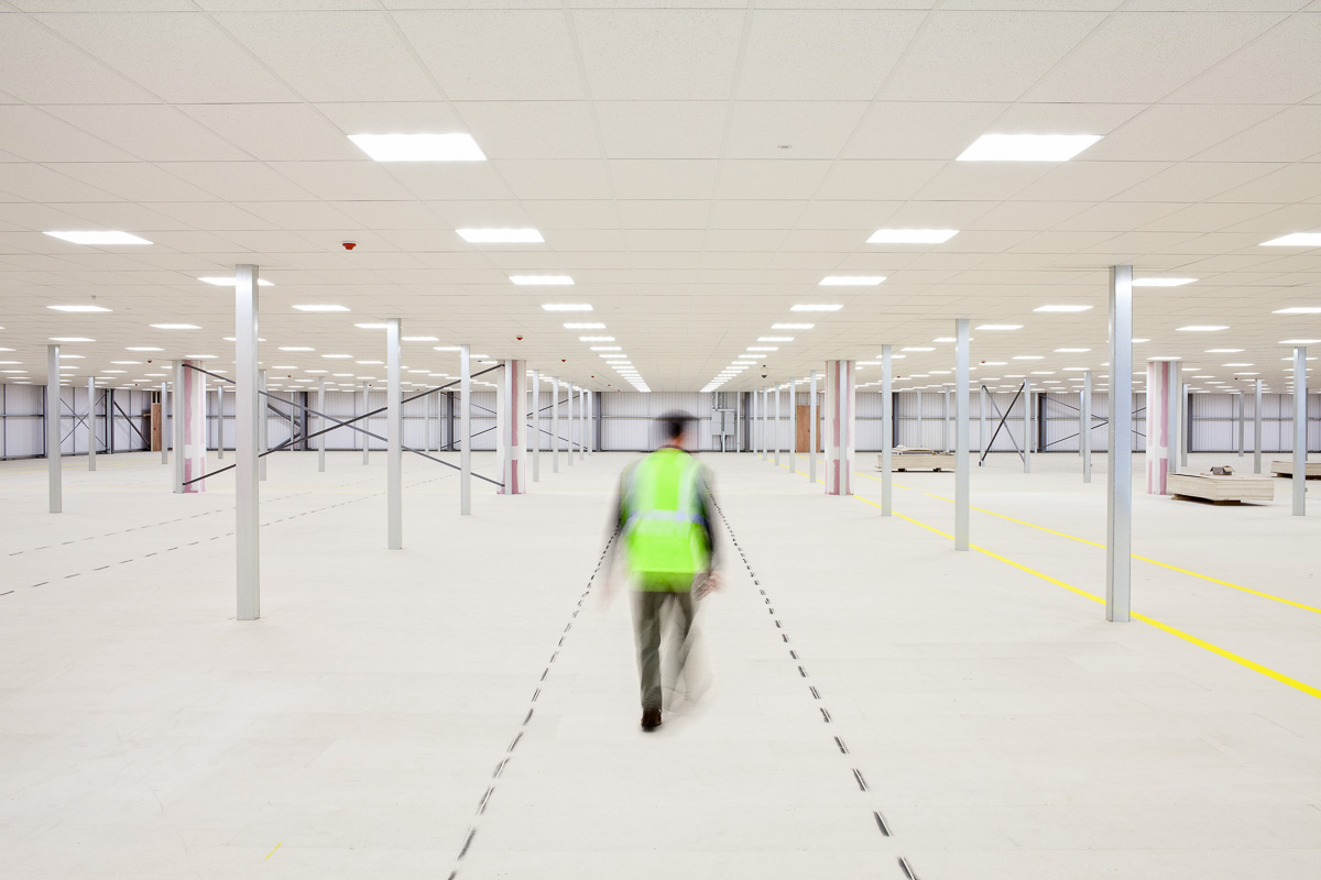 A blurred figure in high-visibility vest walks away from the camera in a large, empty, new warehouse.
