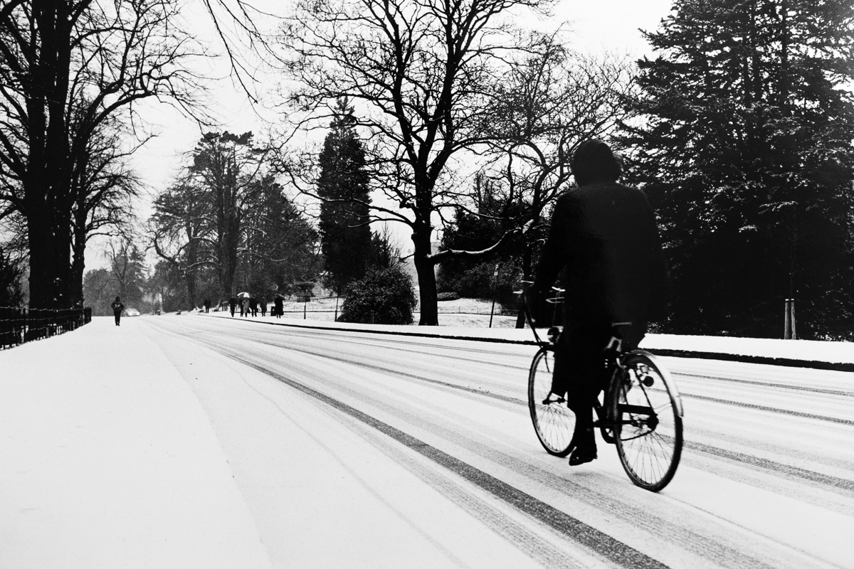 Victoria Park in Bath under snow, circa 1988. A cyclist in black rides in from the right of the image as the road leads into the distance.