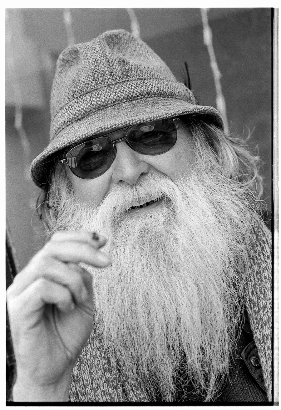 Close-in portrait of a white-bearded gentleman wearing a tweed hat and dark sunglasses and smoking a rolled cigarette, smiling to camera.