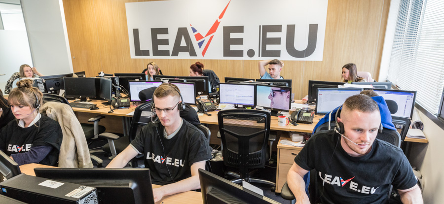 Overview of the call centre at Leave.eu's office in Bristol where fundraisers took pledges from the public. A large Leave.eu sign is on the wall at the back of the room as call handlers sit at desks, watching computer monitors and wearing telephone headsets.