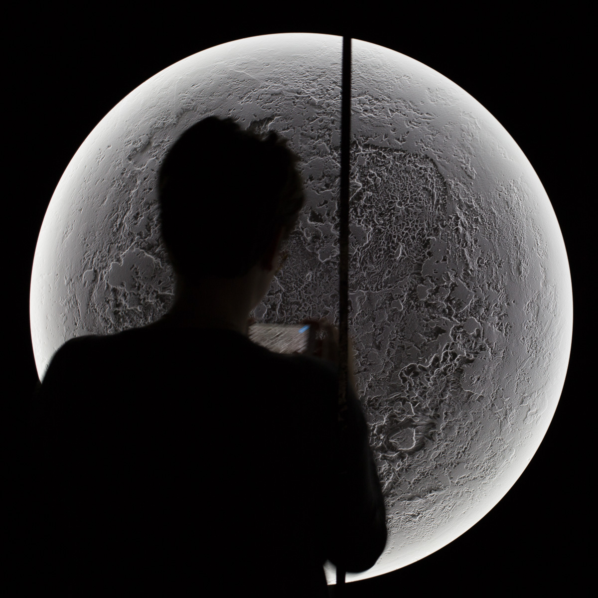 A detail from Illuminator XVII, a modern art installation which resembles the surface of the moon. A silhouetted figure of a lady taking a photo partially obscures the view of the piece.