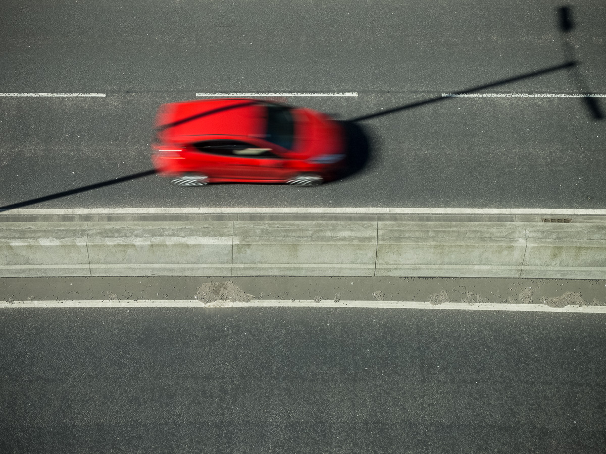 A red car, seen from above, is blurred as it drives along a dual carriageway. Its shape is split by the shadow of an unseen lighting pole which is cast diagonally across the road.
