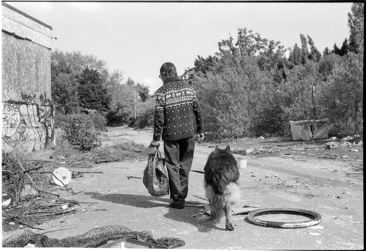 A man and his dog leave the site after exploring the rubbish for any valuable materials such as copper.