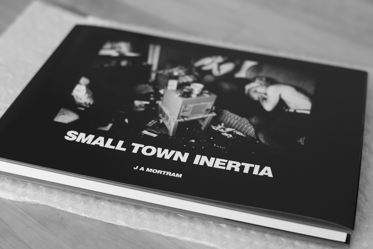 A black and white photo of a copy of Small Town Inertia by J.A Mortam rests on the bubblewrap it arrived in on a coffee table.