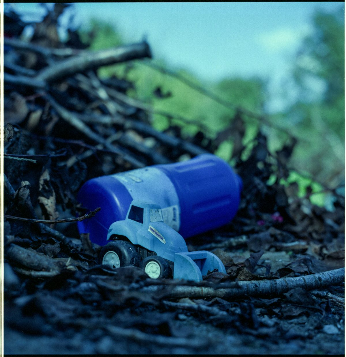 A colour photo of a blue plastic toy tractor and a blue bleach bottle on a pile of twigs.
